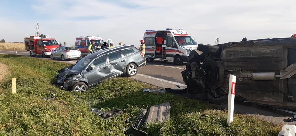 Jeden samochód osobowy w rowie, drugi pojazd poszkodowany leży na boku, w tle służby ratownicze
